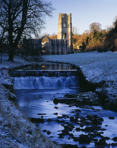 Winter sunlight on Fountains Abbey, North Yorkshire, with sprinkling of snow on ground