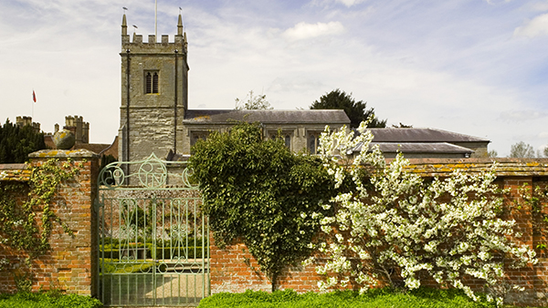 The Church of St Peter and the gates to the Walled Garden at Coughton Court, Warwickshire