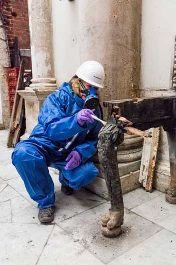 Conservator cleaning the remains of a side table in the Marble Hall. ©National Trust Images/James Dobson