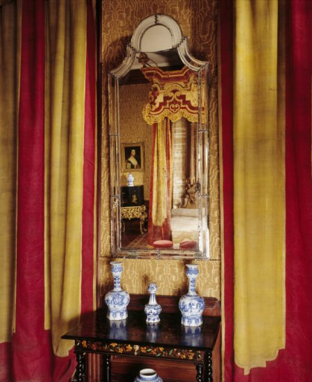 A state bed in the style of Daniel Marot, a japanned cabinet, marquetry table and Delft glazed earthenware vases, in the Damask Bedchamber at Dyrham Park, Gloucestershire. ©National Trust Images/Andreas von Einsiedel