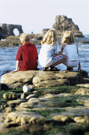 Children sitting on rocks at the Wherry, to the south of Souter Lighthouse. Stack and arch formations are in the distance. MR ©National Trust Images/Joe Cornish