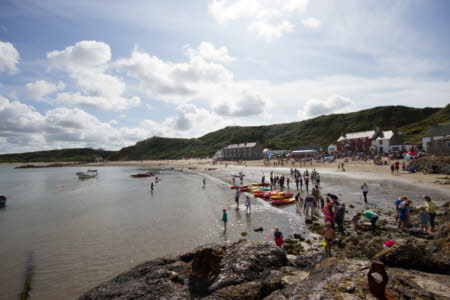 Porthdinllaen beach in Gwynedd with people and canoes on the shore in the summer. ©National Trust Images/Tom Simone