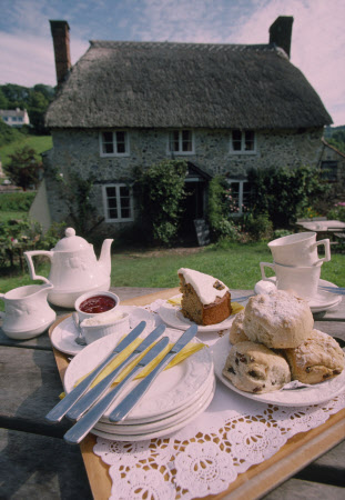 View of a delicious cream tea laid out on the picnic table in front of the Branscombe Tearooms, Devon. Homemade cakes and scones are baked on the premises. ©National Trust Images/David Levenson