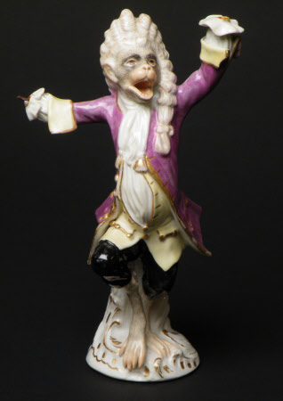 A Meissen figure of a monkey as conductor of an orchestra. Colours, puce and yellow. c.1755.