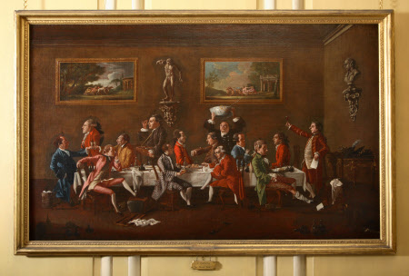 Oil painting on canvas, A Punch Party by Thomas Patch (1725 - 1782), signed and dated, FLORENCE 1760 PATCH PINXITand inscribed with names of sitters. A Punch Party with Sir H. Mainwaring; Earl Cowper; Viscount Torrington; Reverend J. Lipyeatt; Lord Grantham; Sir Brook Bridges, Bt; James Whyte; Jacob Houblon; the Earl of Moray; Mr CharlesHatfield, the landlord; Earl of Stamford; Charles S. Boothby; Sir John Rushout Bt, and Sir Charles Bunbury, Bt. The 5th Earl of Stamford is seen with his friends enjoying an evening at Mr Hadfield's inn called Carlo's near Snato Spirito inFlorence. The artist has introduced a caricature bust of himself on the wall on the right, with thers of a faun. Fourteen figures are depicted, engaged in various activities round a table, for example, Lord Grantham is carrying a pedlar's tray filled with cameos from which Lord Stamford, because he wears it on his finger, has evidently acquired one; but principally they are engaged in drinking the punch provided by the patron Charles Hadfield.On the back wall are paintings of Bacchus and of Silenus in chariots pulled by leopards and tigers respectively; on the wall at the right is a caricature bust of the artist with the ears of a faun, perhaps echoing the replica of the Dancing Faun on the adjacent wall, the original of which is in the Uffizi. The socles on which the sculpture is placed are decorated with the Medici arms.