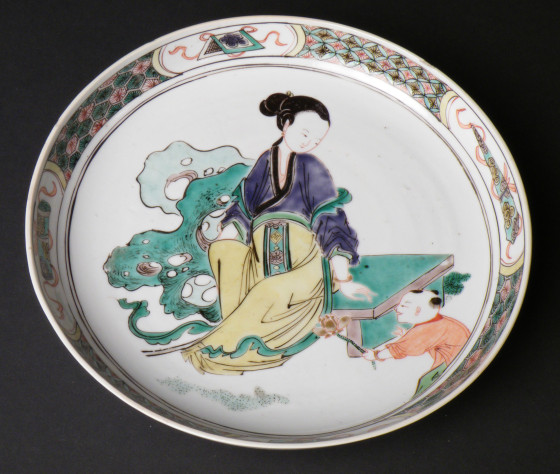 Chinese porcelain saucer dish decorated with a female figure sitting on a bench with a child offering her a lotus flower, Kangxi period (1662-1722), at Polesden Lacey, NT 1245638.1. ©National Trust/Jane Mucklow