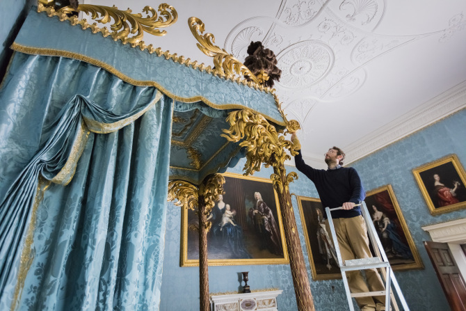 Simon McCormack, conservation manager at the National Trust's Kedleston Hall, puts the finishing touches to the state bed which has returned following restoration. Credit National Trust Images/James Dobson.
