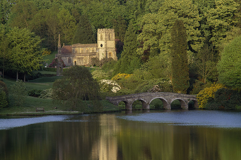A view across the lake at Stourhead towards the Palladian Bridge, with St Peter's Church and the Bristol High Cross (a much restored medieval monument acquired by Henry Hoare II in 1764). ©National Trust Images/Nick Meers
